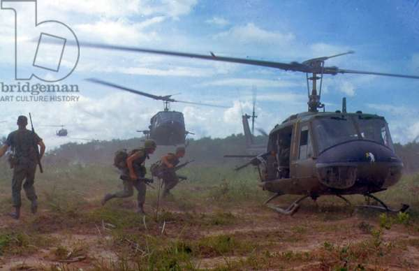 American troops running towards a chopper during the Vietnam War