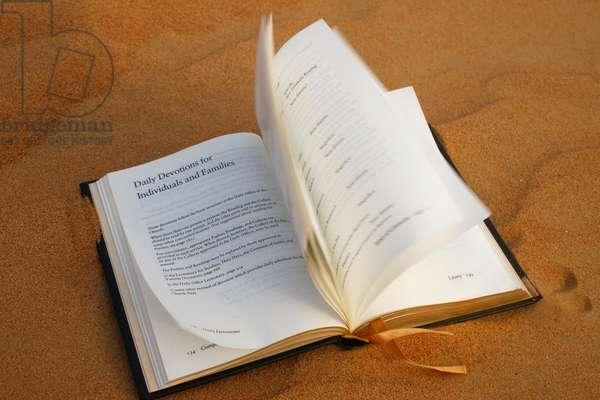 Prayer book on sand (photo)