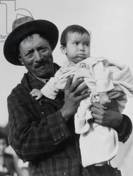 Migrant Mexican father holding his infant child, 1935 (b/w photo)