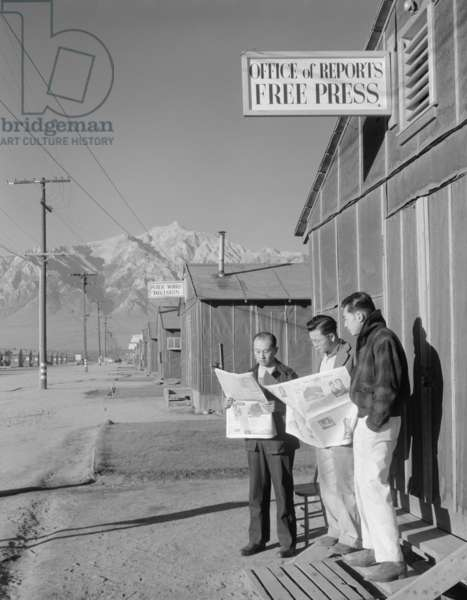 Roy Takeno (Editor) and group reading Manzanar paper [i.e. Los Angeles Times] in front of office, Yuichi Hirata, Nabuo Samamura, Manzanar Relocation Center, California, 1943 (photo)