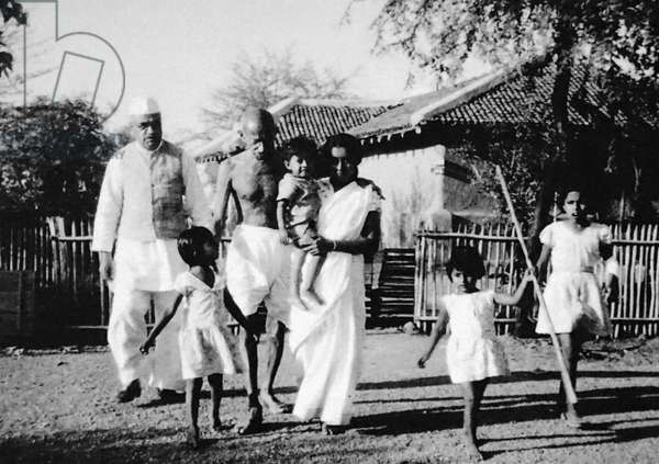 Mahatma Gandhi walking with his grand daughter in law Saraswati; her son Shanti and others at Sevagram Ashram, India