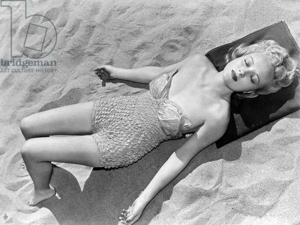 Woman Sun Bathing At The Beach (b/w photo)