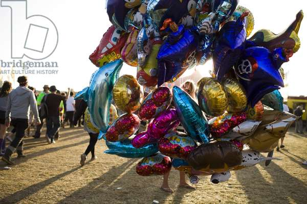 A woman selling balloons in the fields, Reading Festival, 2009, UK.