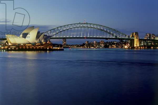 Australia, Sydney, Sydney Harbour Bridge and Sydney Opera House in evening light, panoramic view across water