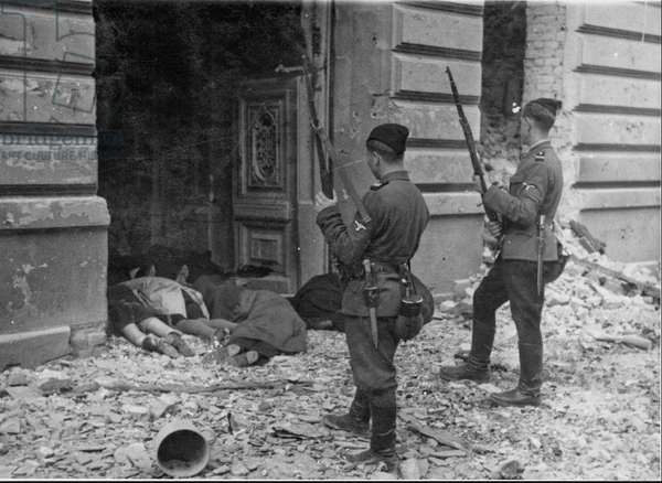 Two members of the Ukrainian SS, known as Askaris, look at the bodies of women and children killed during the uprising in the Warsaw ghetto in 1943 (b/w photo)