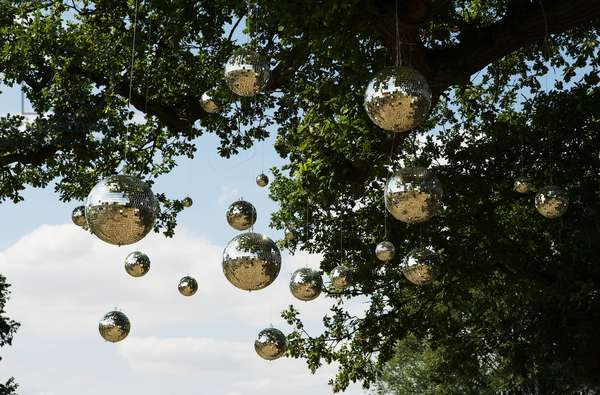 Disco Mirror balls hang from a tree, The Secret Garden Party Festival , Huntingdon Cambridgshire, UK, August 2005.