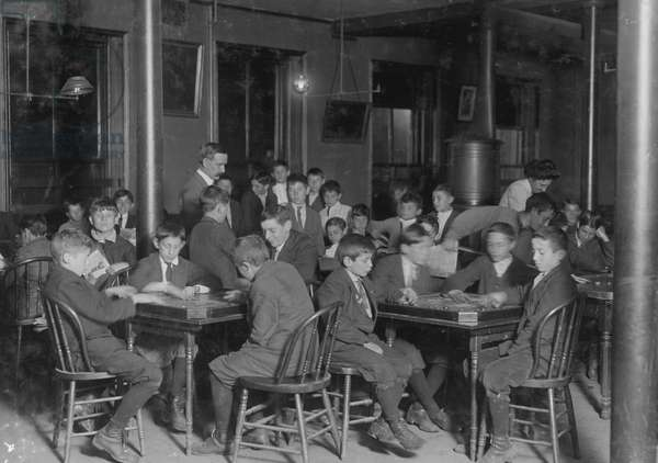 In the Newsboys Reading Room. Boys seated at tables playing gamers. 1909 (photo)