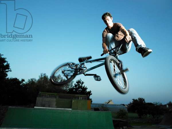 Guy riding a bmx doing a tail-whip on a ramp, UK