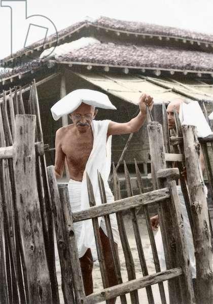 Mohandas Karamchand Gandhi dit Mahatma Gandhi (1869-1948), leader politique et spirituel indien, portant un coussin sur la tete pour prevenir la chaleur, devant le bureau de Satyagraha Ashram, 1940 - Mahatma Gandhi, carrying a pillow on his head due to severe heat, in front of the office hut at Satyagraha Ashram, Sevagram, 1940. ©Dinodia/Uig/Leemage