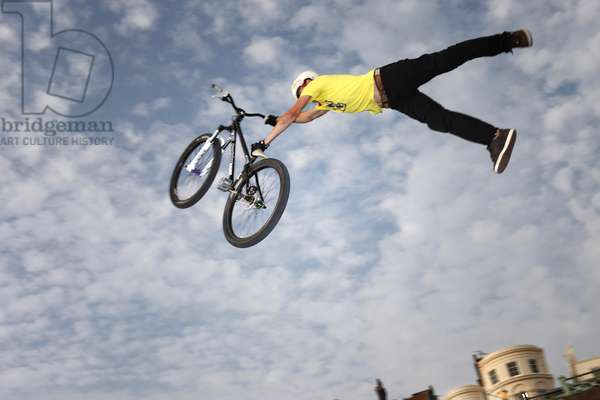 BMX Biker pulls off a trick while flying through the air after jumping off a kicker, Brighton, UK