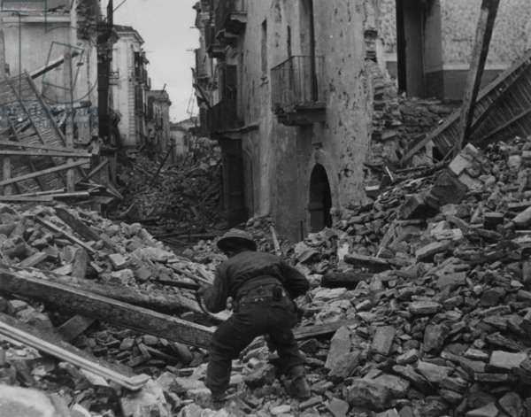 A Soldier Searching Through the Rubble at Cassino, 1942 (b/w photo)