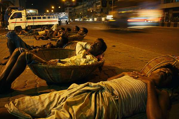 Vegetable porters sleeping in their baskets, on a pavement in Karwan bazaar area of Dhaka city, in Bangladesh. May 23, 2009.  (photo)