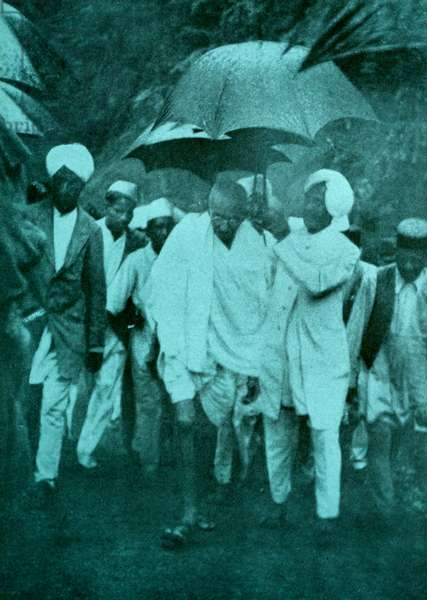 Mahatma Gandhi walks to a protest in the monsoon rain.
