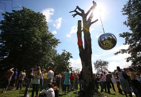 Crowds and giant mirrorball, at a festival, London UK