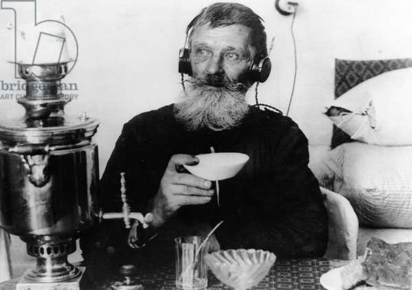 A Worker of the 'Sibir' Match Factory with a Radio Set, Drinking Tea from his Samovar, Near Tomsk, Sibeia, 1928.
