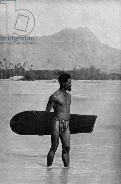 Hawaii. Hawaiian rider of the waves and his surf board.  1920