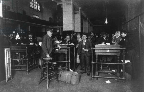 Ellis Island Immigration Station, New York, USA: Immigration officers , after examining documents, giving immigrants their final discharge, 1902.