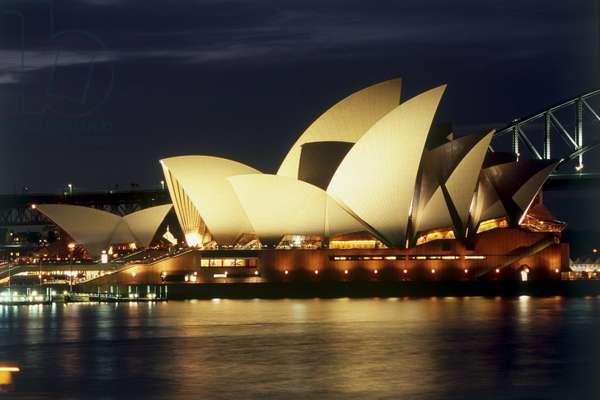 Australia, Sydney, Sydney Opera House illuminated at night, view across water