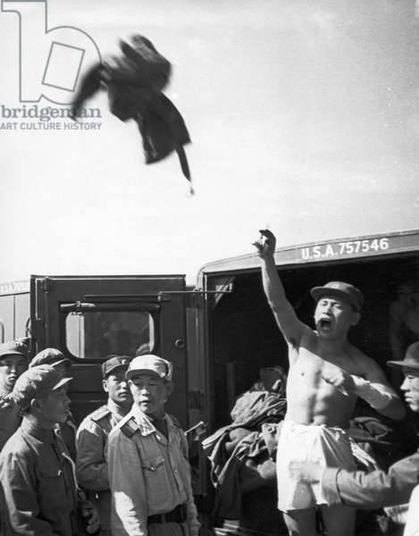 The North Korean repatriates throw away every item of clothing issued by the Americans while arriving at the reception area of the Korean and Chinese side, August 1953