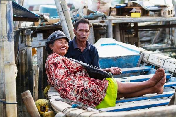 Couple in a boat in Sunda Kelapa Harbour, Jakarta, Java, Indonesia (photo)
