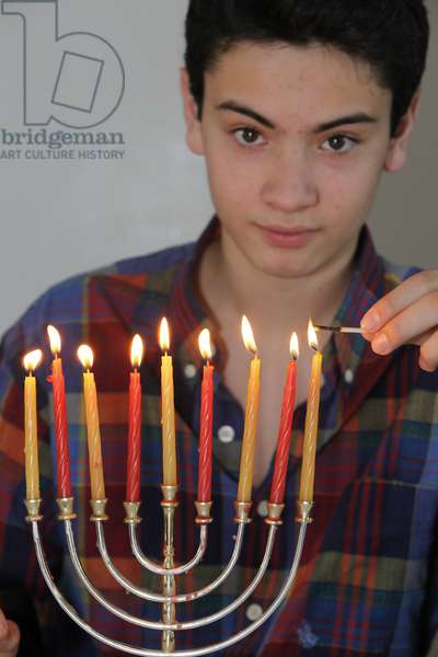Teenager lighting Hannukah candles (photo)