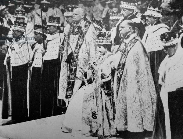 H.M. the Queen wearing St. Edward's Crown and holding the Royal Sceptre and the Rod of Equity, waits to receive the homage of her peers after her Coronation.