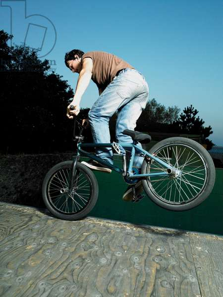 A guy riding a bmx doing a nose pick on a ramp, UK
