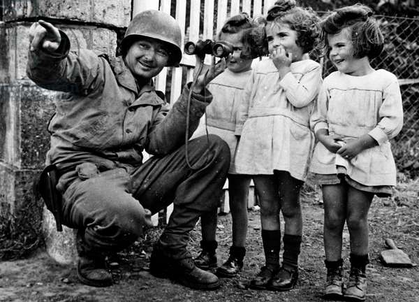 Soldier holding binoculars up to three little girls, 1944