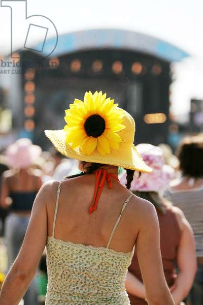 The back of a woman wearing a flower in her hat, at a music festival, UK