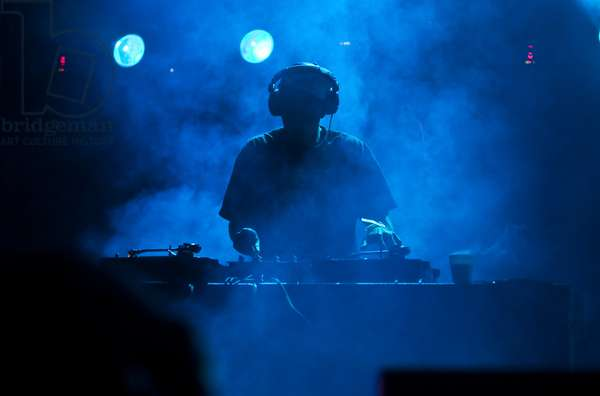 Silhouette of a DJ at a music concert, UK