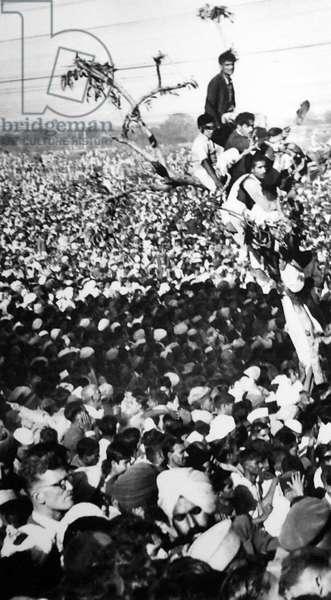 Crowds watch the cremation of Mohandas Karamchand Gandhi, India