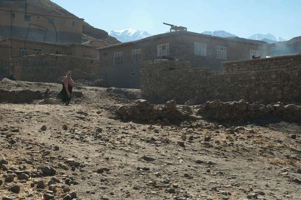 Woman by Stone Houses in Baghe Afghan, Parwan Province, Afghanistan (photo)