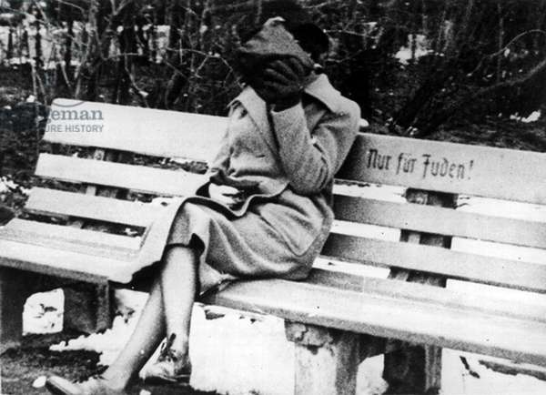 Female hides her face from people as she sits on a Jew only bench, 1938