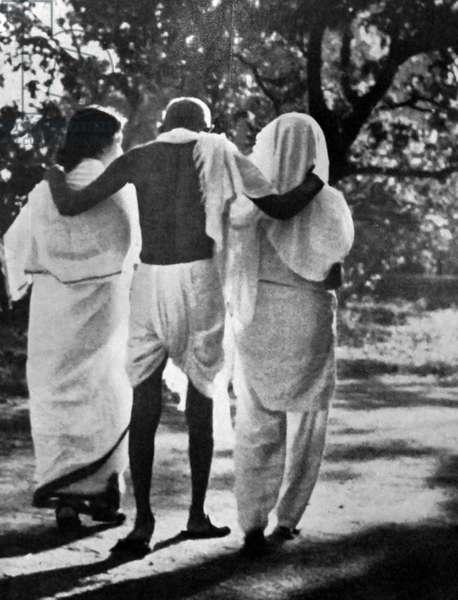 Mohandas Karamchand Gandhi with his nieces walking in a garden 1948