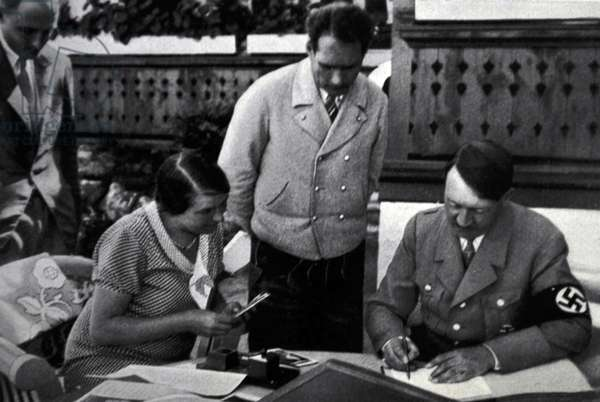 Adolf Hitler signs state documents watched by a secretary and Deputy Nazi Party leader, Rudolf Hess at Berchtesgaden