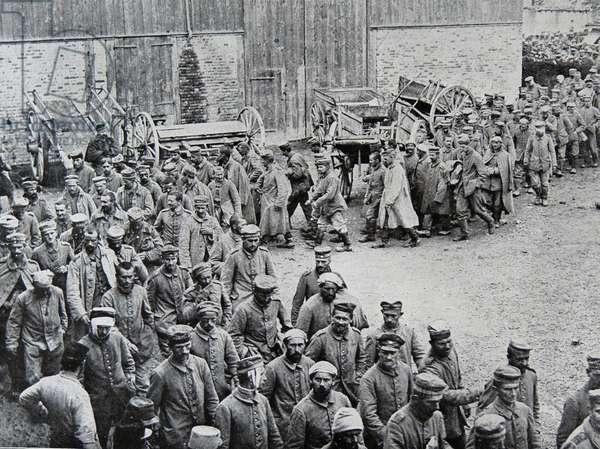 German prisoners of war parade through a farmyard