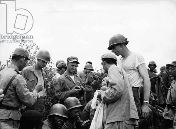 Korean War. American soldiers receiving cigarettes from the Korean People's Army at a joint celebration after the signing of the armistice. August 10, 1953.