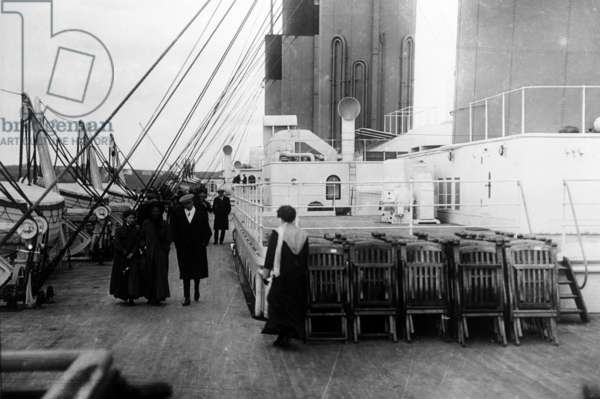 Passengers walk on the deck of the SS Titanic