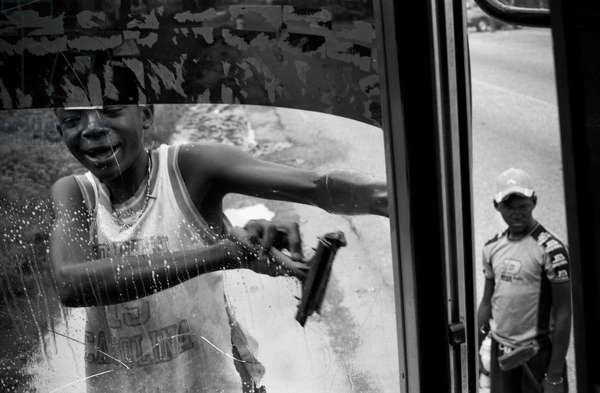 A boy cleaning the windshield of a bus in Caracas, the capital city of Venezuela. Venezuela is a tropical country on the northern coast of South America. It is a continental mainland with numerous islands located off its coastline in the Caribbean Sea. Venezuela is among the most urbanised countries in Latin America. The vast majority of Venezuelans live in the cities of the north, especially in the capital Caracas which is also the largest city. Caracas, Venezuela.  (photo)