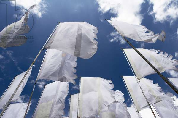 Shot from below, white flags flutter against a deep blue sky and fluffy clouds at a music festival, UK
