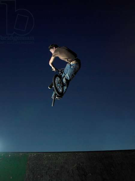BMXer pulling large lookback air while two others look on, UK
