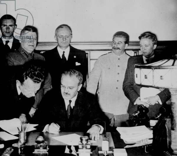 Soviet Foreign Commissar Vyacheslav Molotov signs the German-Soviet nonaggression pact: Joachim von Ribbentrop and Josef Stalin stand behind him. Moscow, August 23. 1939.World War II
