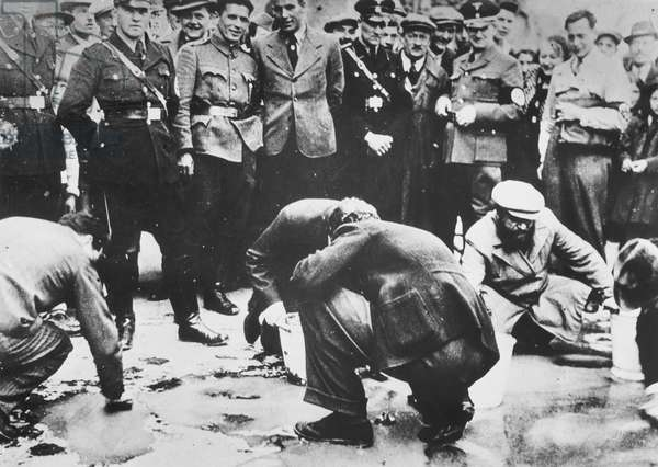 Austrian Nazis and local residents look on as Jews are forced to get on their hands and knees and scrub the pavement, 1938.