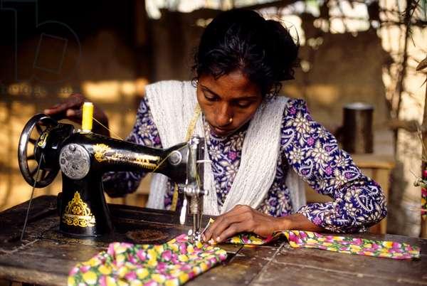 A rural woman stitches cloth. Bangladesh.  (photo)