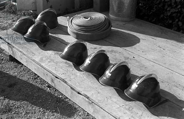 Firefighter's helmets and hose (b/w photo)