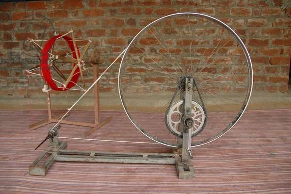 India: The charkha popularized by Mahatma Gandhi lives on in villages near Nagpur, Maharashtra, India, and is used for spinning threads. The available tools such as a cycle wheel and chain is used in making this tool. The maintenance and upkeep is simple as is the availability of spare parts. 07-Mar-07.  (photo)