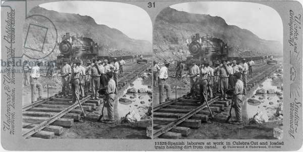 Construction of the Panama Canal: Spanish labourers at work in the Culebra Cut (Gaillard Cut) . A loaded steam train hauls spoil from the site. The canal, a great feat of civil engineering, was opened in 1914. Photograph.