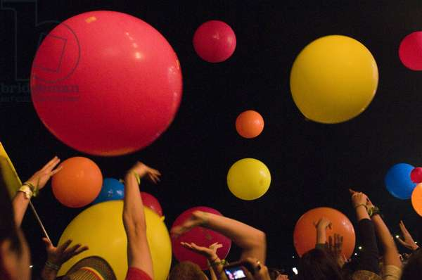 Crowd punching inflatable balls into the air, at a music festival, UK