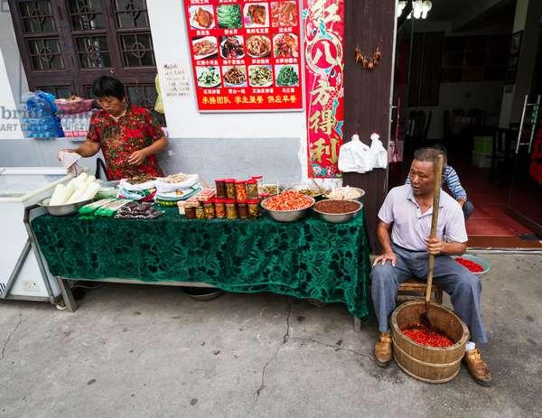 Man crushing hot peppers (photo)