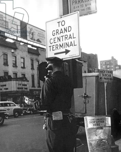 New York, c.1946 A policeman next to a Grand Central Terminal sign calls in to headquarters on a police phone.  (b/w photo)